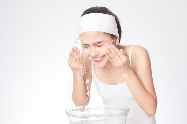 Beautiful woman is washing her face on white background Premium Photo