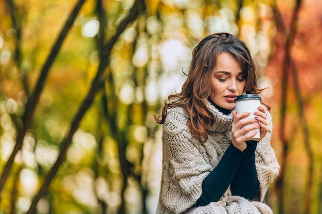 Beautiful woman in a knitted sweater holds a glass of hot coffee in the park in the autumn. Premium Photo