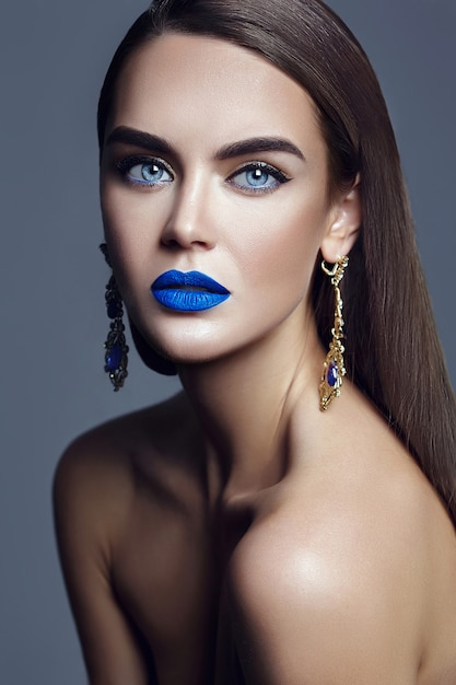 Beautiful woman lady with blue lips and jewelry Free Photo