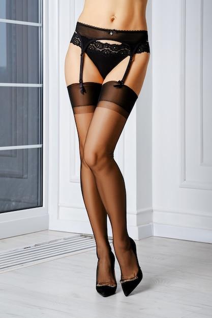 엘라 스탄, 가터 벨트 및 팬티가없는 구식 스타킹의 아름다운 여자 다리 프리미엄 사진