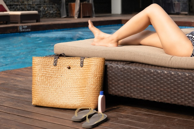 Beautiful woman legs lying on sunbed with beach bag and sunscreen and sandal. Premium Photo