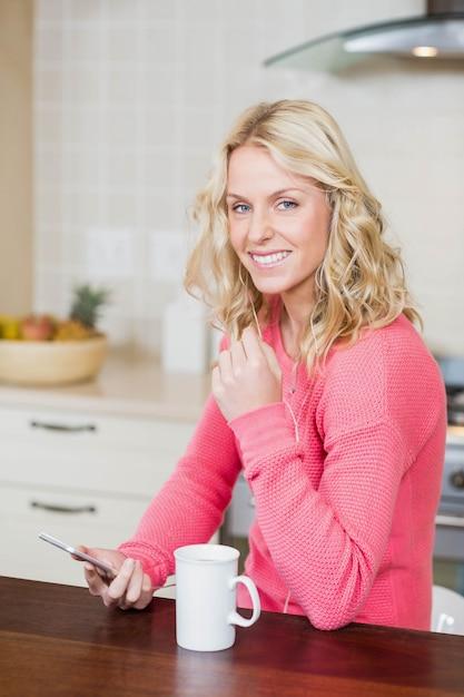 Beautiful woman listening to music in the kitchen Premium Photo
