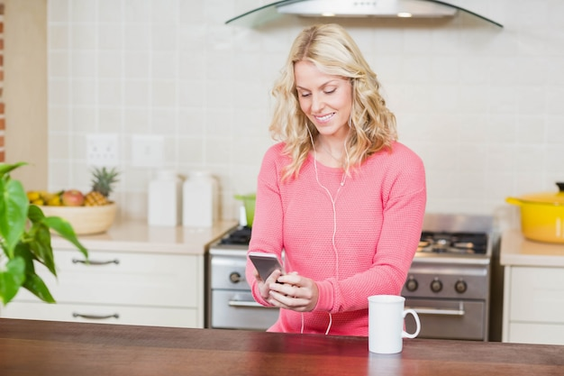 Beautiful woman listening to music in the kitchen Premium Photo