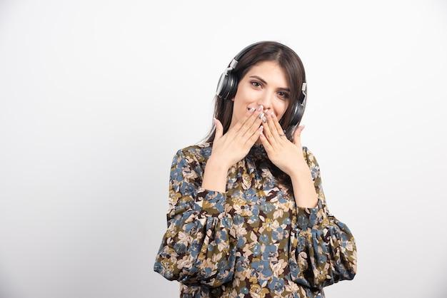 Bella donna ascoltando la canzone e chiudendo la bocca su sfondo bianco. Foto Gratuite