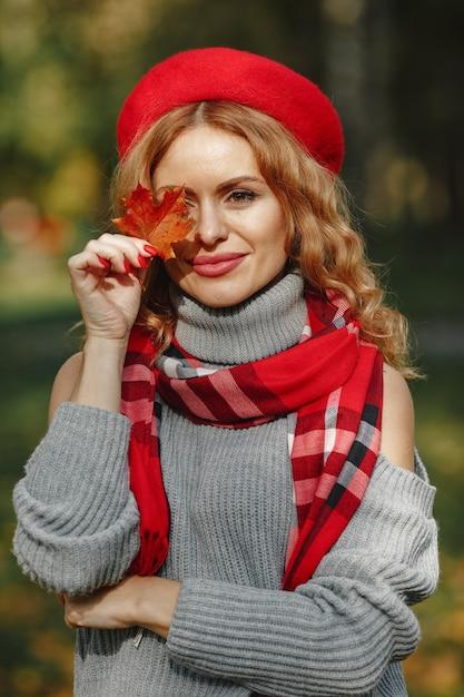 Bello sguardo della donna. ragazza alla moda in un berretto rosso. signora tenere foglia in mano. Foto Gratuite