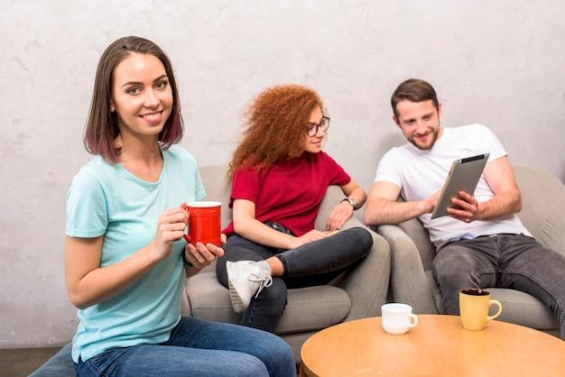 Bella donna che guarda l'obbiettivo che tiene tazza di caffè che si siede con gli amici guardando la tavoletta digitale Foto Gratuite