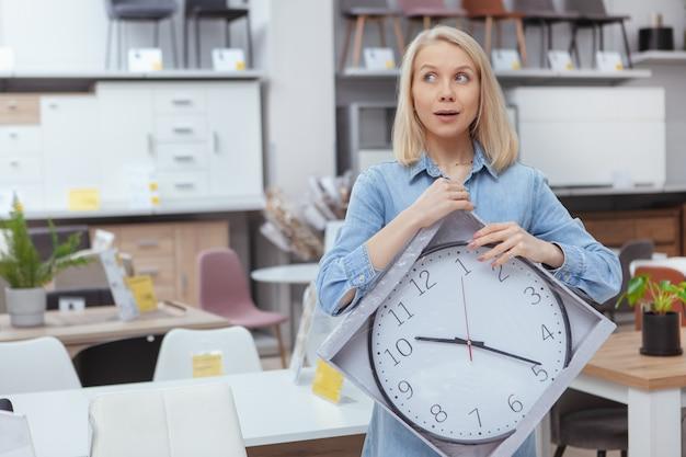 Красивая женщина ищет возбужденных, держа большие настенные часы, покупая товары для дома в универмаге Premium Фотографии