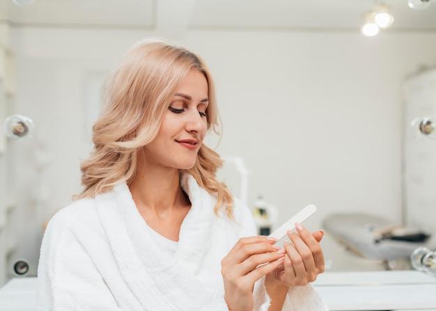 Bella donna che guarda la sua sana manicure Foto Gratuite