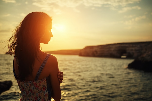 Beautiful woman looking into the distance at sunset ...