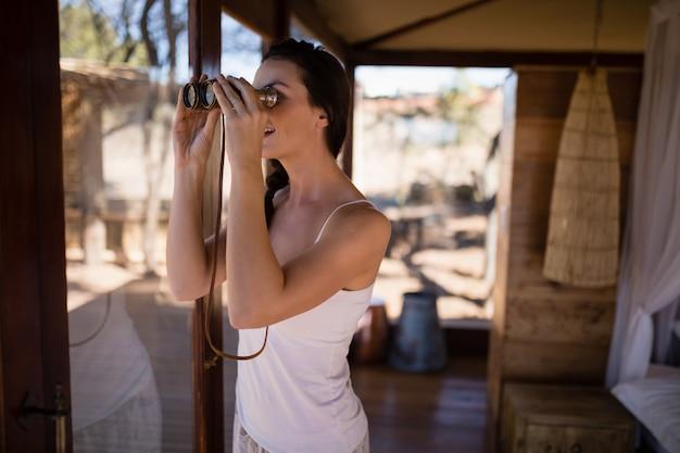 Beautiful woman looking through binoculars from window Free Photo