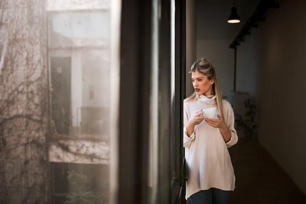 Beautiful woman looking through window, holding a mug. Premium Photo
