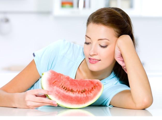 Красивая женщина смотрит на красный арбуз на кухне Бесплатные Фотографии