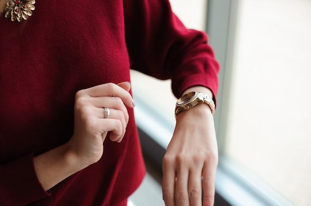Красивая женщина смотрит на часы у окна Premium Фотографии