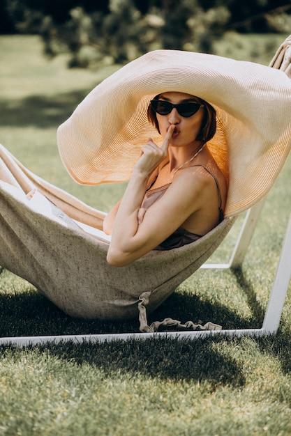 Beautiful woman lying in hammock wearing big sunhat Free Photo
