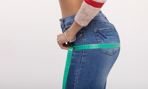 그녀의 엉덩이 측정하는 아름 다운 여자. 흰 벽에 고립 된 체중 감량 개념입니다. 프리미엄 사진