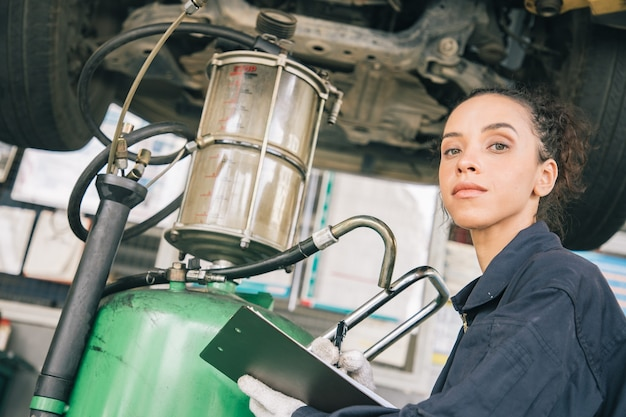 Beautiful woman mechanics in uniform is working in auto service with lifted vehicle and paper reporting. Premium Photo