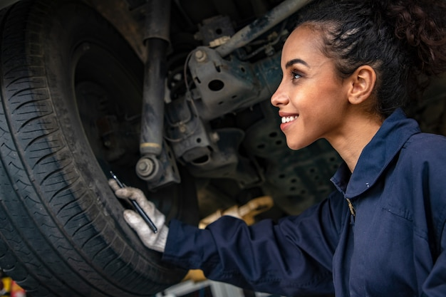 Beautiful woman mechanics in uniform is working in auto service with lifted vehicle and reporting. Premium Photo