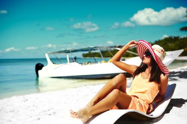 Beautiful woman model sunbathing on the beach chair in white bikini in colorful sunhat behind blue summer water ocean Free Photo