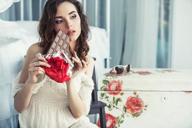 寝室のインテリアに対して手にダークチョコレートのタイルを持つ美しい女性モデル Premium写真
