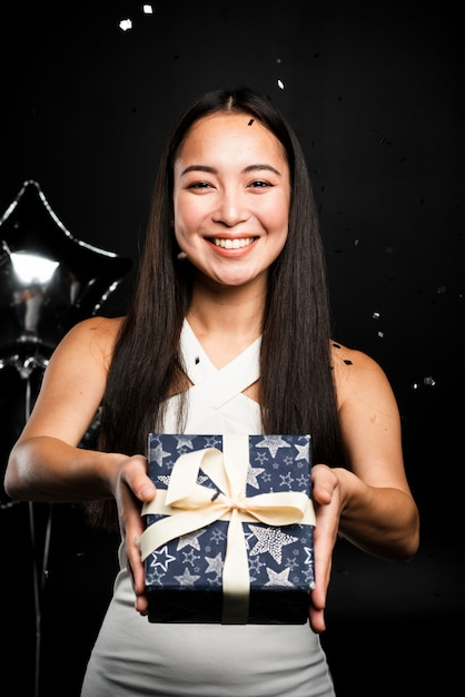 Beautiful woman offering present at new years Free Photo