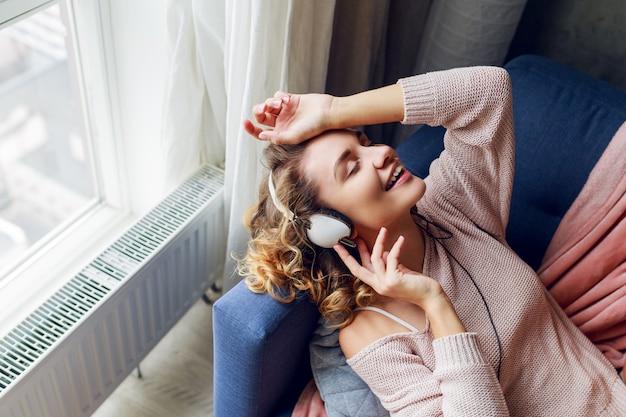 音楽を聴くソファの上の美しい女性 無料写真