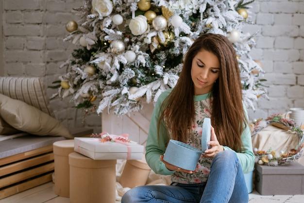 美しい女性が自宅でクリスマストレでギフトを開きます 無料写真