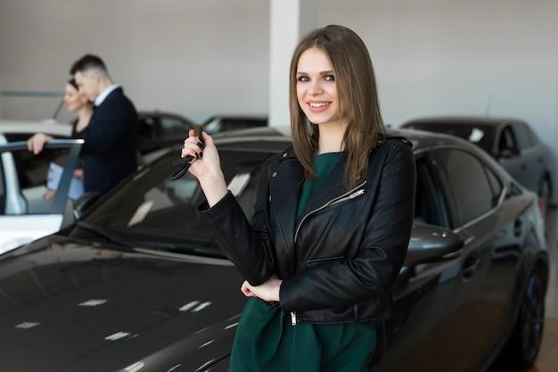 Стенд красивая женщина или продавец автомобилей держит новый автомобильный дистанционный ключ в автосалоне Premium Фотографии