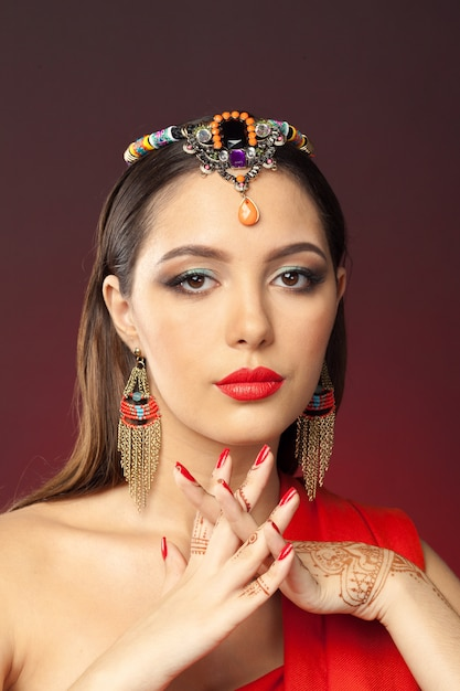 Beautiful woman in oriental style with mehendi on dark Premium Photo