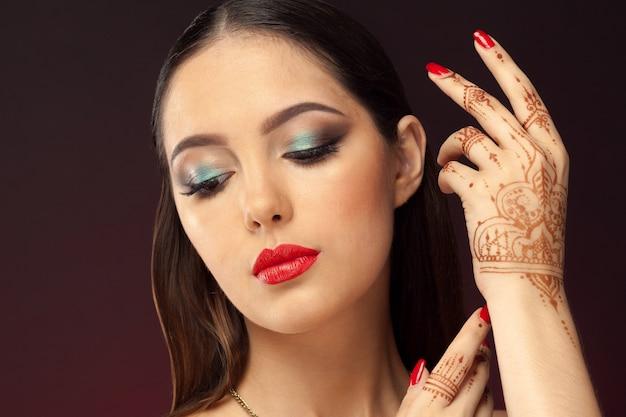 Beautiful woman in oriental style with mehendi on dark Premium Photo