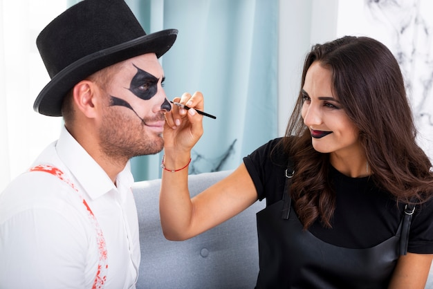 Beautiful woman painting husbands face for halloween Free Photo