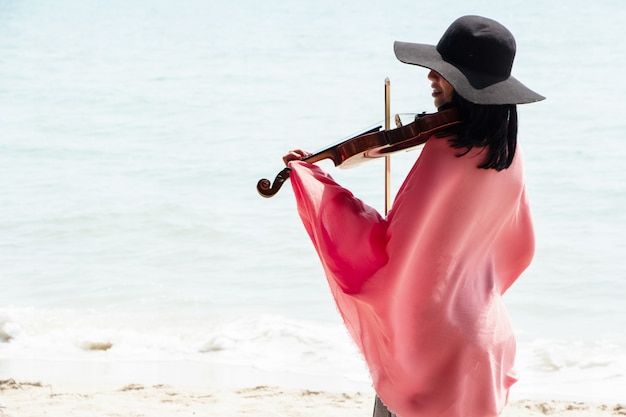 The beautiful woman playing violin on the beach Premium Photo