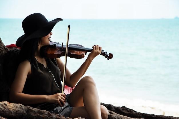 The beautiful woman playing violin on the beach Premium Photo