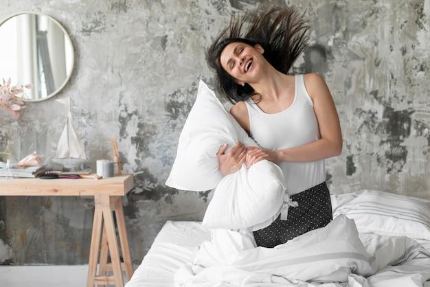 Bella donna che gioca con il cuscino Foto Gratuite