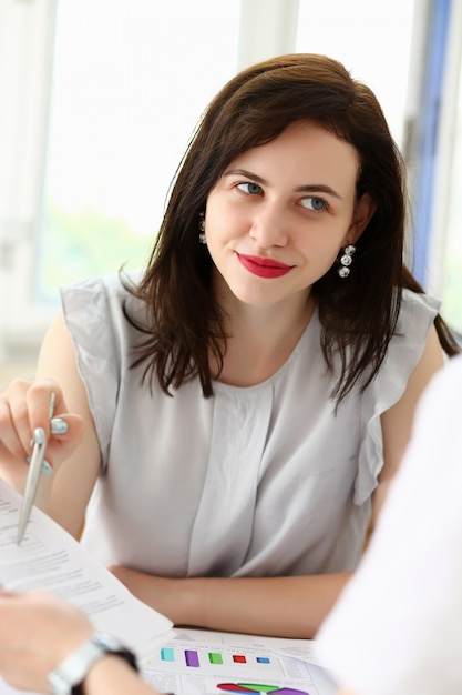 Beautiful woman portrait at workplace examining Premium Photo