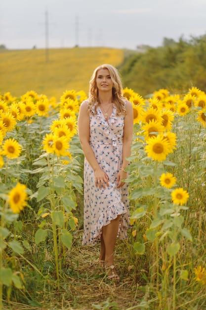 日当たりの良い夏の日にひまわりと農業分野で美しい女性ポーズ 無料写真