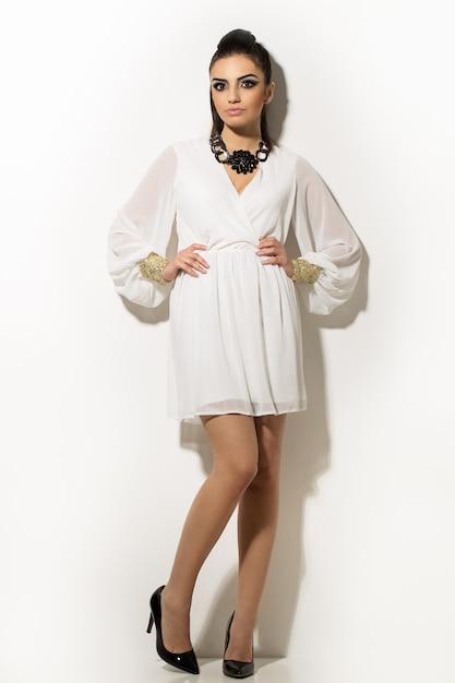 Beautiful woman posing in white dress Free Photo