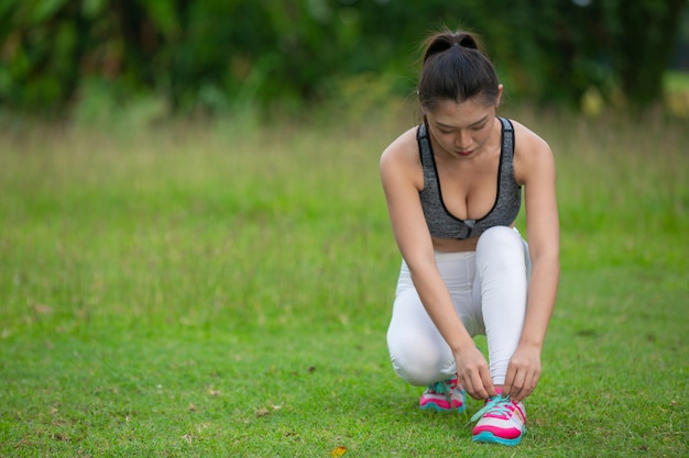 A beautiful woman preparing to exercise in the park. Free Photo