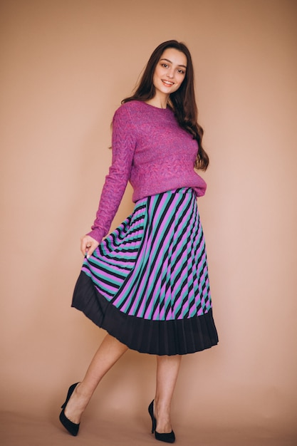 Beautiful woman in a purple sweater and skirt Free Photo