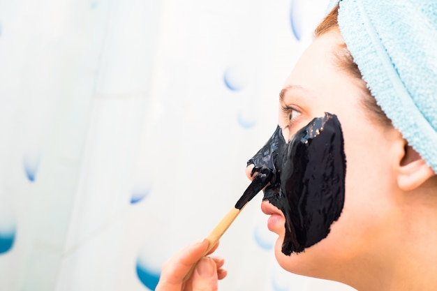Beautiful woman puts mask on her face Premium Photo
