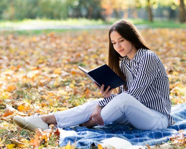 Красивое чтение женщины в парке Бесплатные Фотографии