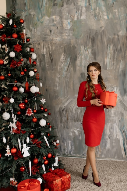 Beautiful woman in red dress poses before rich christmas tree Free Photo