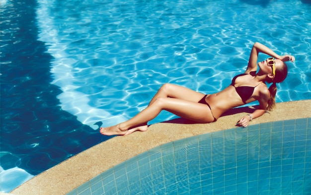 Beautiful woman relaxing in the pool in summer photo for Pool show in long beach