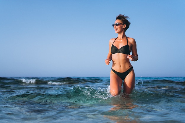 Beautiful woman running out of the ocean Free Photo