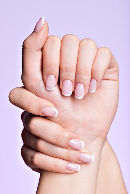 프랑스 매니큐어와 매니큐어 살롱 후 아름다운 손톱을 가진 아름다운 여자의 손 무료 사진