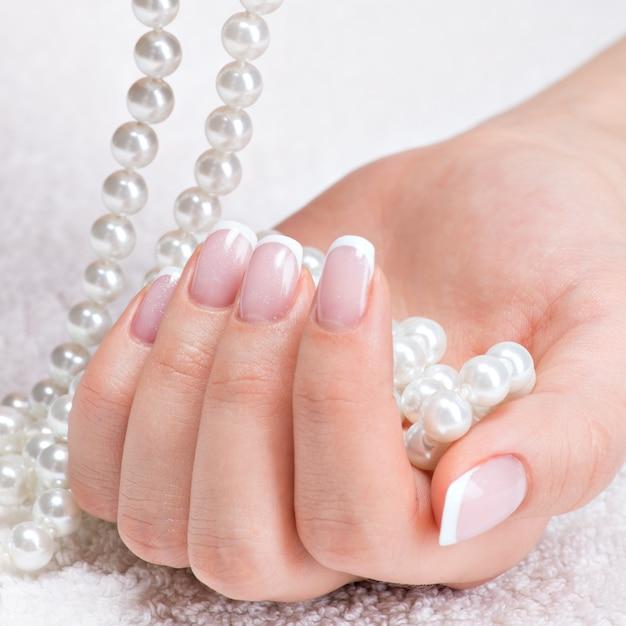 Le unghie della bella donna con bella french manicure e perle bianche Foto Gratuite