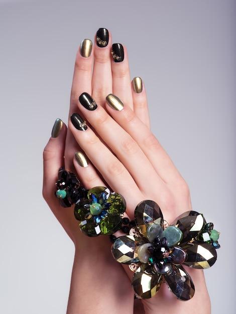 Le unghie della bella donna con manicure e gioielli creativi Foto Gratuite