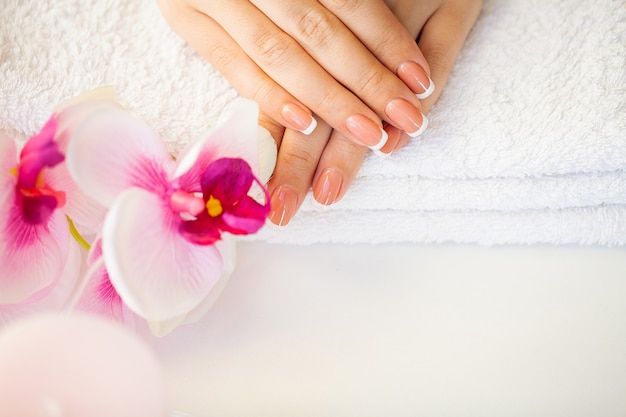 Beautiful woman's nails with french manicure, in beauty studio Premium Photo