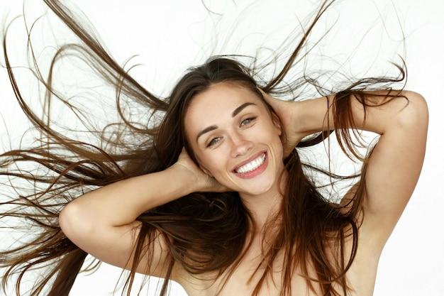 Красивая женщина качает волосы на белом фоне Бесплатные Фотографии