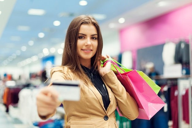 Beautiful woman showing credit card in shopping mall Free Photo