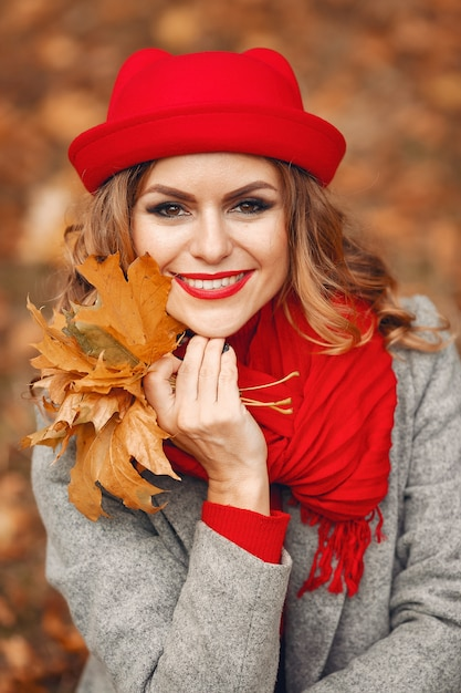 Beautiful woman sitting in a autumn park Free Photo